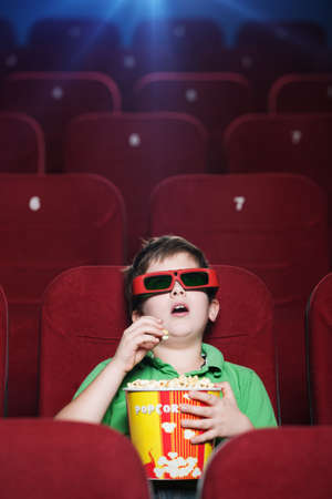 sits on a chair: A boy with popcorn is watching a movie at the cinema Stock Photo