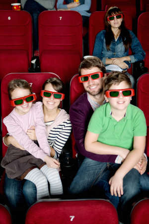 Happy family with two children watching a movie