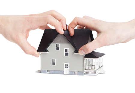 divides: Concepto de bienes ra�ces - las dos manos tratando de dividir a casa, aislados