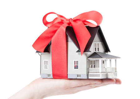 hands holding house: Real estate concept - Hand holding house architectural model with red bow on it, isolated