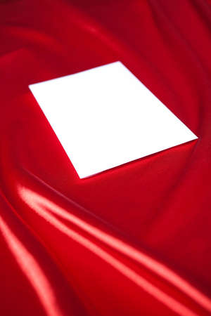 White envelope over red silk background photo