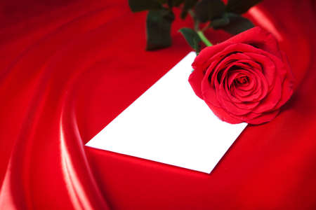 White envelope and red rose over abstract silk background photo