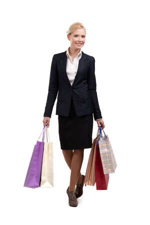 Businesswoman in a black suit holding shopping bags, isolated on white background photo