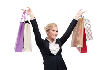 Young businesswoman in a black suit holding shopping bags, isolated on white background photo