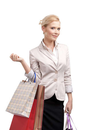 looking at watch: Businesswoman in a light beige suit holding shopping bags, isolated on white background