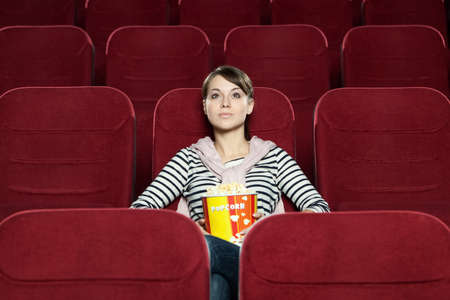 Young woman with a snack food waiting for a friend at the cinema Stock Photo - 13648461
