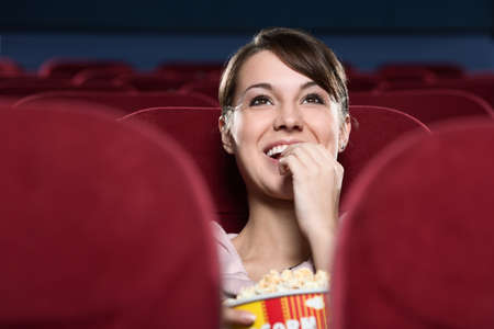 Young woman with popcorn watching a movie photo