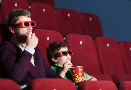 family movies: A boy with father eating popcorn in 3D movie theater