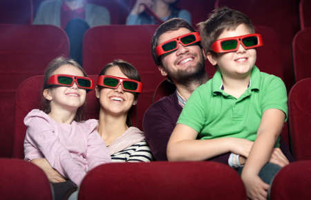 theater seat: Smiling family in the 3D movie theater Stock Photo