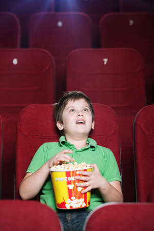 Happy boy with popcorn watching a movie photo