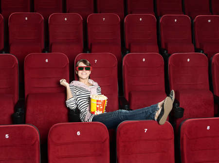 sits on a chair: Smiling woman in 3D movie theater sitting alone in the row Stock Photo