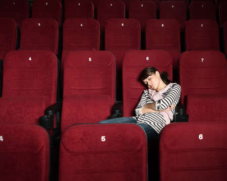 sits on a chair: Overexhausted woman in the movie theater