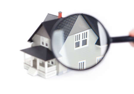 nobody real: Real estate concept - hand holding magnifying glass in front of the house architectural model, isolated
