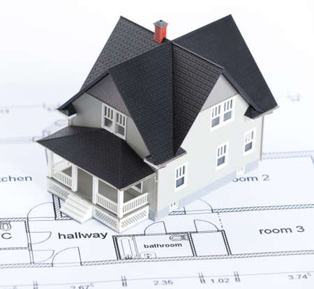Real estate concept - construction plan with  house architectural model on it photo