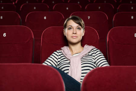 Beautiful girl watching a movie at the cinema photo