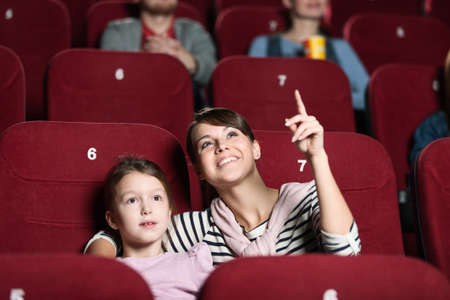 Smiling girl with mother at the cinema photo