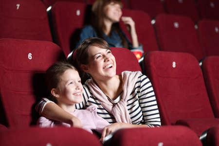 CINE: Loughing madre e hija en el cine viendo una película Foto de archivo