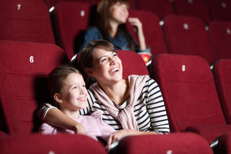 family movies: Loughing mother and daughter at the cinema watching a movie