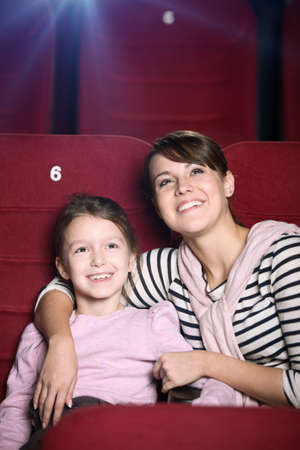 Mother and child are watching a movie at the cinema photo