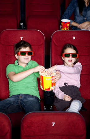 Children sharing popcorn in the 3D movie theater photo