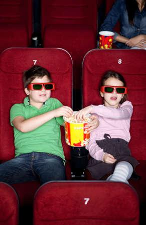 enfant banc: Enfant partageant pop-corn dans la salle de cin�ma 3D