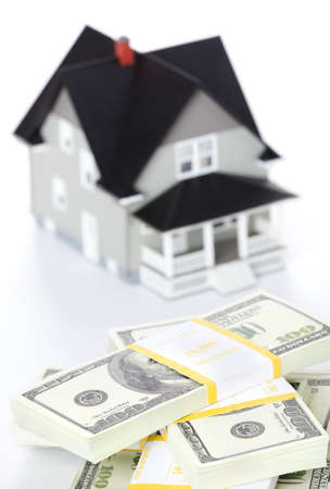Real estate concept - bundles of dollars in front of house architectural model, isolated Stock Photo - 13746924