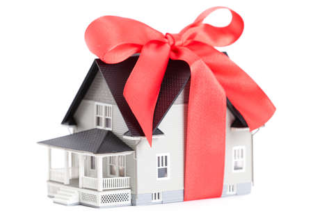 nobody real: Real estate concept - house architectural model with red bow on it, isolated Stock Photo