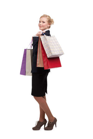 Young businesswoman in a black suit holding shopping bags, isolated on white photo