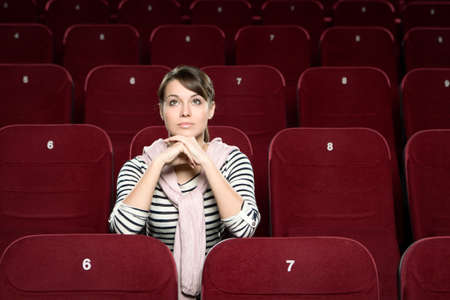 sits on a chair: A woman sitting in the movie theatre Stock Photo