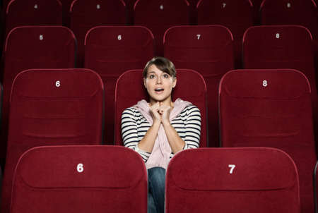 Funky woman watching a movie alone at the cinema photo