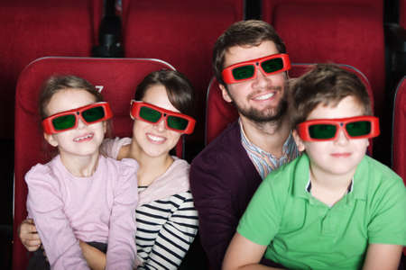 movies: Happy family spending time in 3D movie theater