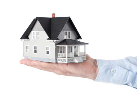 realty residence: Real estate concept - hand holding house architectural model, isolated Stock Photo