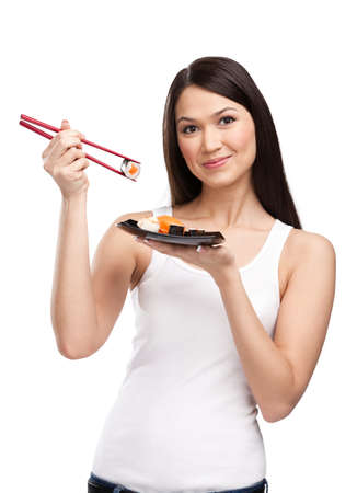 Black-haired girl holding sushi with a chopsticks, isolated on white background photo