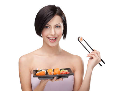 sushi plate: Young woman holding sushi with a chopsticks, isolated on white background Stock Photo