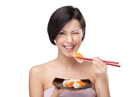 Black-haired girl eating sushi with a chopsticks, isolated photo