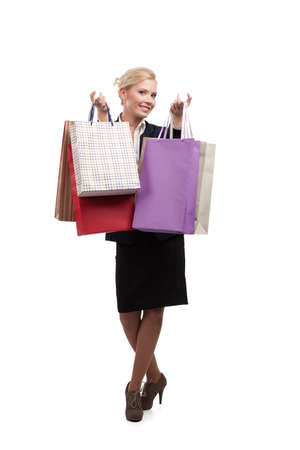 Young attractive business woman in a black suit holding shopping bags, isolated on white background photo