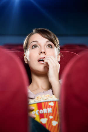 Young woman with popcorn at the cinema photo