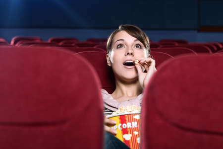Young surprised woman eating popcorn in the movie theater photo