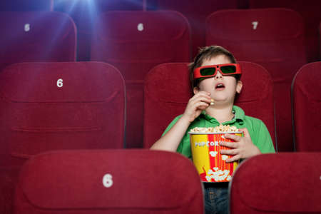 Surprised boy eating popcorn in the movie theater photo