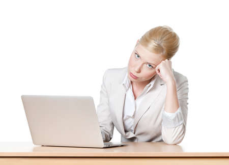 Tired young businesswoman sitting at a office table with laptop, isolated photo