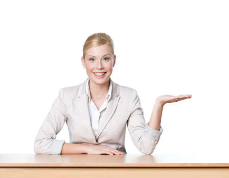Young business woman sitting at a office table, isolated