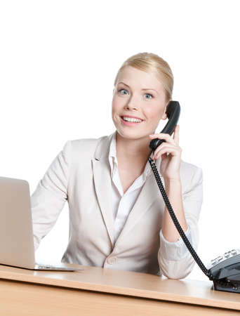 Young business woman sitting at a office desk and holding phone handset, isolated photo