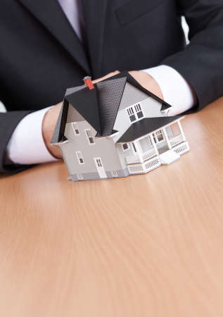 Real estate concept - businessman hands behind house architectural model Stock Photo - 13900979