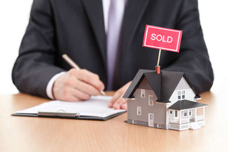 selling house: Real estate concept - business man signs contract behind house architectural model Stock Photo