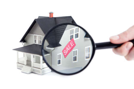 Real estate concept - hand holding magnifying glass in front of the house architectural model, isolated Stock Photo - 13900983