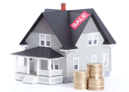 lending: Realty concept - stacks of coins in front of house architectural model, isolated
