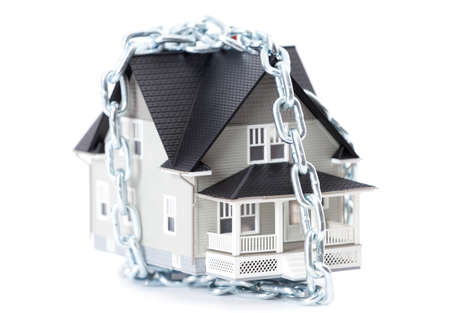 Real estate concept - chain around the home architectural model, isolated photo