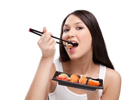 Brunette girl eating sushi with a chopsticks, isolated Stock Photo - 13894519