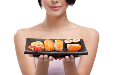 Young girl holding plate of sushi in her hands photo