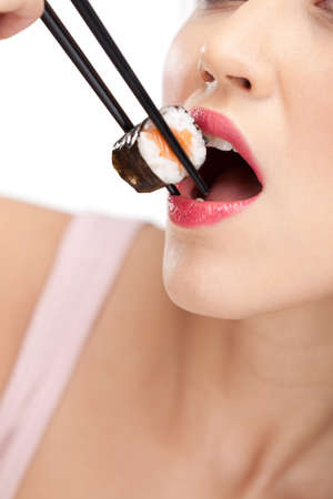 Young woman holding sushi with a chopsticks, closeup, isolated photo